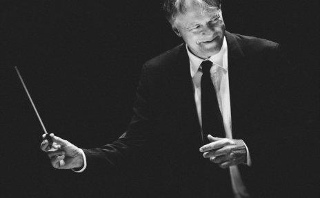 Der Dirigent Thomas Hengelbrock hält einen Dirigentenstab in der Hand und lächelt zur Seite.