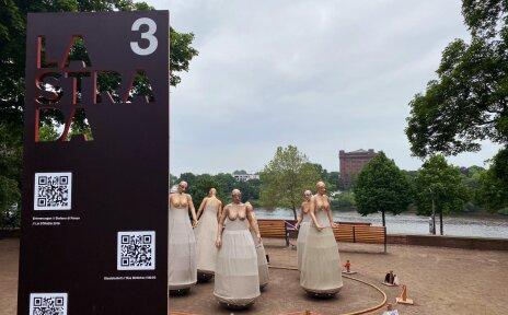 """Mehrere Skulpturen stehen im Kreis. Hierbei handelt es sich um ein Kunstwerk im Rahmen der Veranstaltung """"LA STRADA"""". Im Vordergrund steht ein Schild, auf dem QR-Codes zu sehen sind."""