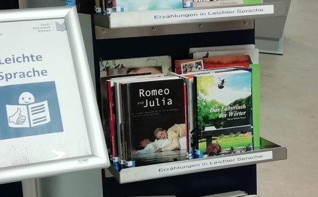 """Ein Bücherregal in einer Bibliothek mit Büchern in Leichter Sprache. Davor steht ein Schild mit der Aufschrift """"Leichte Sprache""""."""