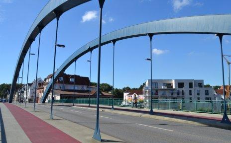 Eine Brücke mit rotem Radweg, blauer Himmel.