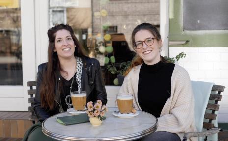 Zwei junge Frauen sitzen vor einem Caféan einem Tisch mit zwei Getränken.