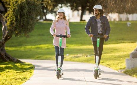 Zwei junge Menschen fahren auf e-Rollern durch eine grüne Kulisse
