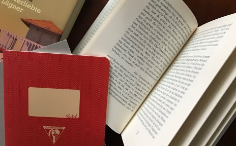 Tisch mit Büchern und Notizheft