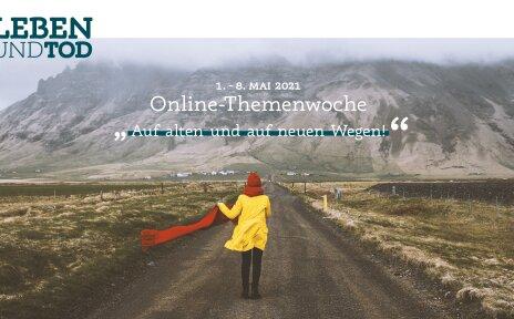 Eine Frau steht mit einem roten Schal auf einem langen Schotterweg. Im Hintergrund ist ein Berg.