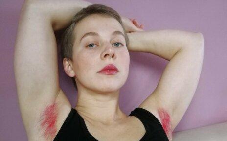 Zu sehen ist eine Frau mit pinken Axelhaaren. Ihre Arme hat sie über dem Kopf verschränkt. Sie trägt ein schwarzes Oberteil