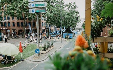 Foto des gesperrten Bereichs der Martinistraße mit Liegestühlen, Rollrasen und Zelten.