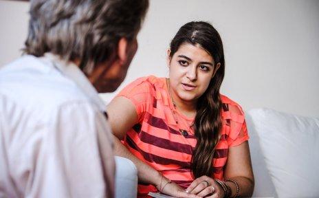 Eine junge Frau sitzt auf einem Sofa. Sie spricht mit einem Mann, der ihr gegenüber sitzt.