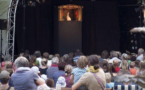 Menschen schauen sich Puppentheater auf der Bühne an.
