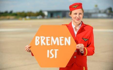 """Eine junge Frau in Stewardessen Uniform hält ein Schild in der Hand auf dem """"Bremen ist"""" steht."""