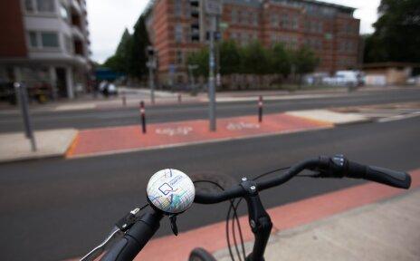 Im Vordergrund ein Fahrradlenker mit Fahrradklingel, im Hintergrund Straßen mit markierten Radwegen