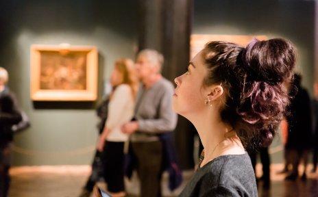 Eine Frau betrachtet ein Gemälde in einer Museumsausstellung.