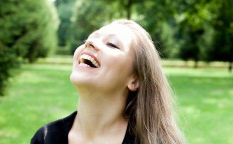 Bild von einer blonden Frau in einem grünen Park die den Kopf in den Nacken wirft und lacht.