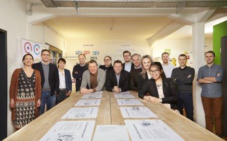 Eine große Gruppe Menschen, das Team von myEnso, steht um einen Tisch herum und lächelt in die Kamera.