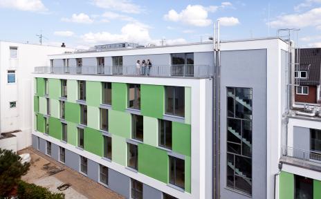 Ein Wohnungskomplex bestehend aus fünf Etagen. Die Fassade ist in einem hellen und dunklen grün, sowie grau, gestrichen. Oben ist ein Balkon auf dem stehen drei Personen.
