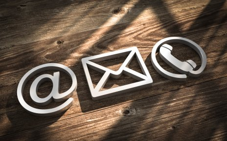 Ein @-Zeichen, ein Briefsymbol und ein Telefonhöhrer-Symbol vor einem hölzernen Hintergrund