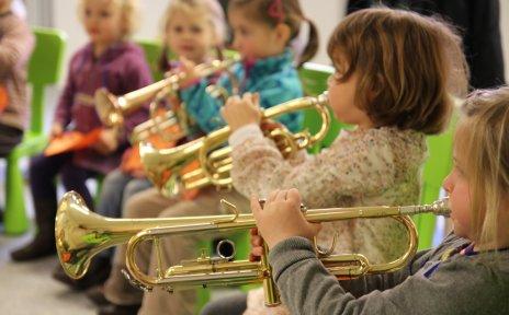 Kleine Kinder sitzen nebeneinander auf Stühlen und spielen Trompete.
