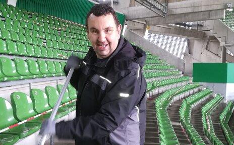 Ein Mann reinigt die Sitze eines Fußballstadions.