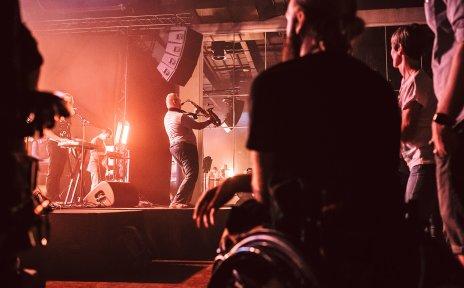 Zuschauende bei einem Konzert. Auf der Bühne ist der Auftritt einer Band zu sehen.