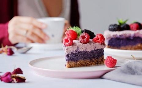 Zu sehen ist ein Stück Kuchen. Er ist belegt mit Himbeeren und Brombeeren.