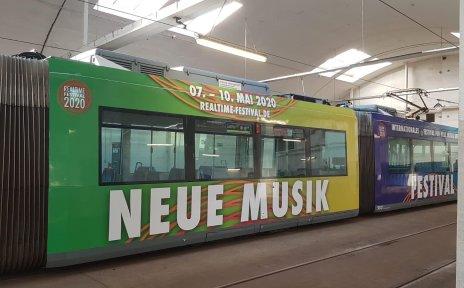 Eine Bahn mit weißen Schriftzügen auf grün, blau und gelber Farbe.