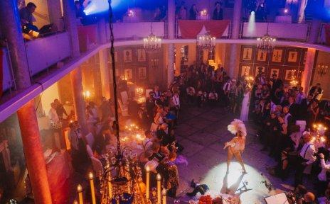 Von einem Balkon wurde in die Menge fotografiert. Eine Frau in einem Federkostüm steht im Mittelpunkt.