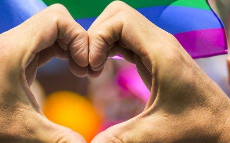 Auf dem Bild ist eine Regenbogenflagge abgebildet sowie Hände, die ein Herz formen.