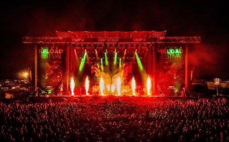 Die Bühne auf dem Reload Festival. Es ist dunkel und rote und grüne Scheinwerfer strahlen auf die Bühne. Vor der Bühne stehen viele Menschen und hören sich ein Konzert an.