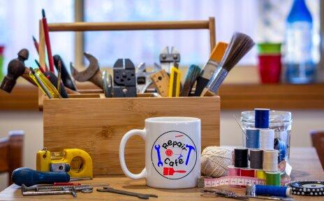 Ein kleiner Werkzeugkoffer mit allerhand Werkzeugen, davor Schrauben, Garn, Scheren und ein Bescher mit der Aufschrift Repair Café