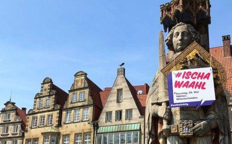 Der Bremer Roland auf dem Marktplatz behangen mit einem Werbemittel zur Wahl am 26. Mai
