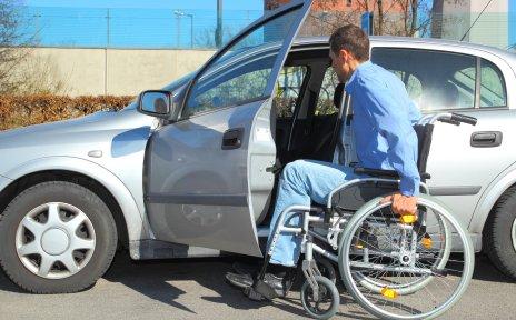 Rollstuhlfahrer beim Einsteigen ins Auto.