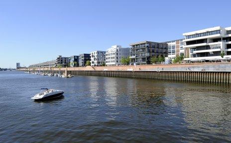 Blick auf den Europahafen, im Vordergrund ein kleines Motorboot auf der Weser, im Hintergrund Büro- und Wohngebäude.