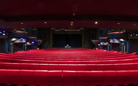 Ein großer Theatersaal mit roten Sitzreihen.