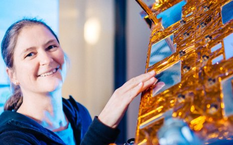 Eine Frau fasst einen Satelliten an.
