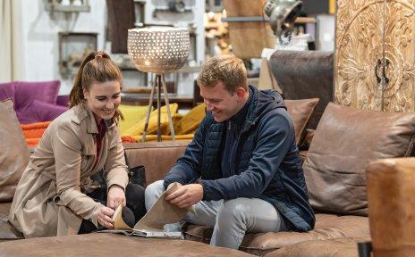 Ein Mann und eine Frau sitzen auf einem Sofa und schauen sich verschiedene Stoffe an.