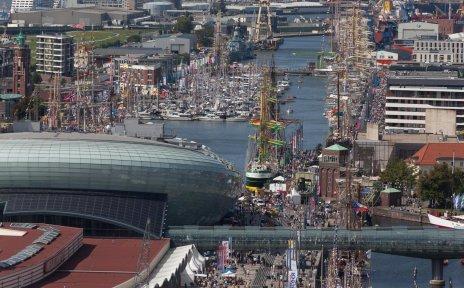 Die Sail in Bremerhaven in Großaufnahme. Viele Schiffe sind dort angelegt und einige Besucher*innen laufen an den Schiffen entlang.