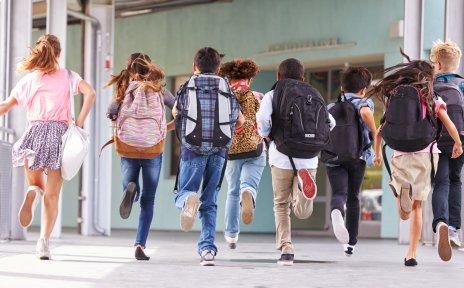 Schulkinder mit Schulranzen auf dem Rücken laufen