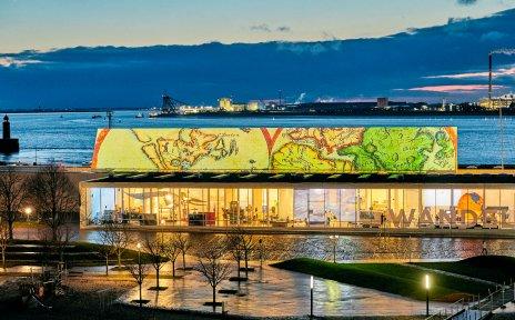 Aufnahme des hell erleuchteten Schifffahrtsmuseums in der Abenddämmerung. Im Hintergrund sind Meer und Hafen zu sehen.