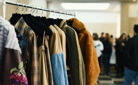 An einer Kleiderstange hängen verschiedene Kleidungsstücke.
