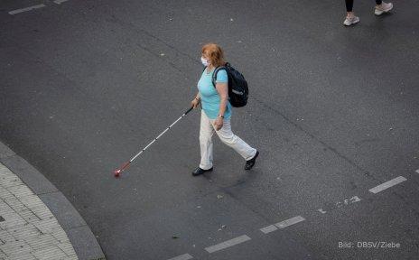 Eine Frau mit Sehbeeinträchtigung kreuzt eine Straße und orientiert sich mit einem Langstock. Sie trägt einen Mund-Nase-Schutz.