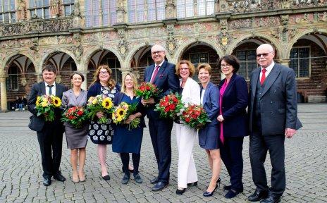 Menschen posieren mit Blumensträußen vor dem Rathaus