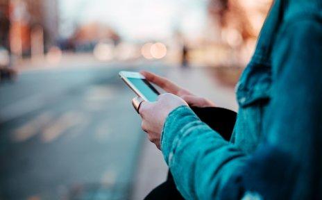 Eine Person steht an einer Straße. Sie hält ein Smartphone in der Hand.