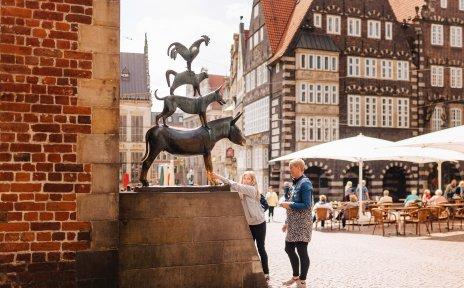 Ein Mädchen und eine Frau stehen vor den Bremer Stadtmusikanten.