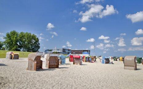 Bunte Strandkörbe stehen an einem weißen Sandstrand.