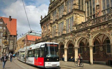 Eine Straßenbahn fährt vor dem Rathaus über den Marktplatz Bremen
