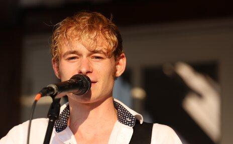 Ein Mann mit blonden Haaren singt in ein Mikrofon.
