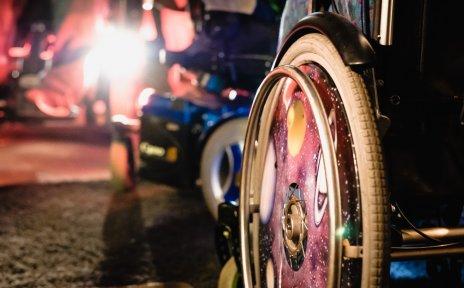Auf einer inklusiven Party: Ausschnitt eines Rollstuhls, im Hintergrund sieht man helle Lichter.