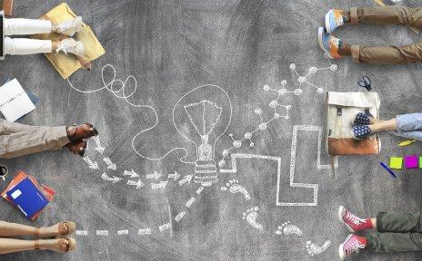 Auf dem Bild sieht man mehrere Personen die kreativ arbeiten und eine Kreidezeichnung von einer Glühbirne.