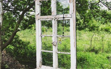 Ein Fenster mit weißem Fensterrahmen ist an einem Baum über einer grünen Wiese aufgehängt.