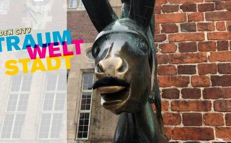 """Man sieht den Esel der Bremer Stadtmusikanten, dem ein Schnurrbart angeklebt wurde, und den Schriftzug """"TraumWeltStadt"""" in blau, pink und gelb."""