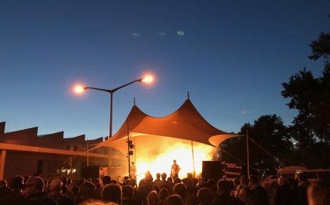 Eine Band spielt im Abendlicht vor vielen Menschen auf einer Bühne.